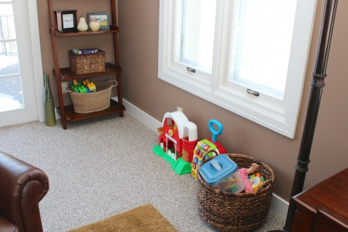Toys in the family room.  Books & blocks are in baskets on the shelves, her shopping cart is tucked into a corner on the opposite side of the room and everything else is lined up along this wall.