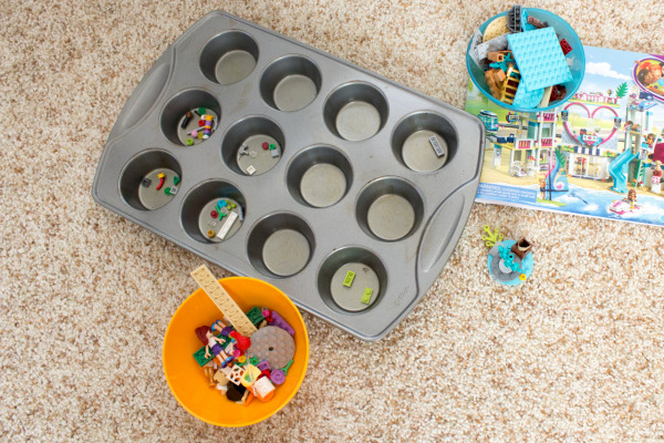 Using muffin tins & small bowls to sort out Lego pieces for a new set.