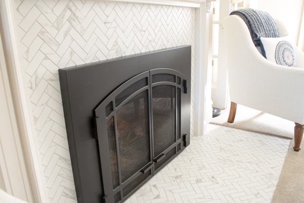 The finished fireplace tile - Florida Tile Precious Calcutta Herringbone Mosaic.